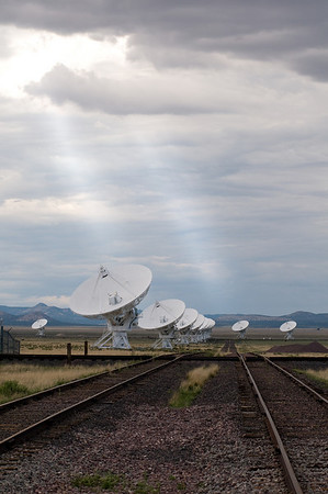Sunrays shine through the clouds onto the VLA, illuminating both the telescopes and the train tracks used to move them around the observatory.