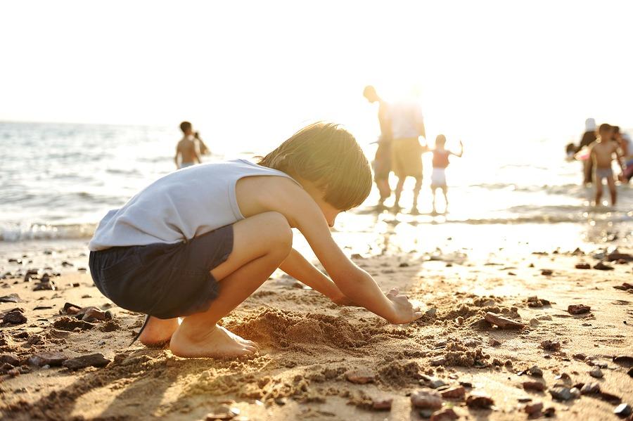 Kid on beach in sand playing, people around, summer hot nice tim