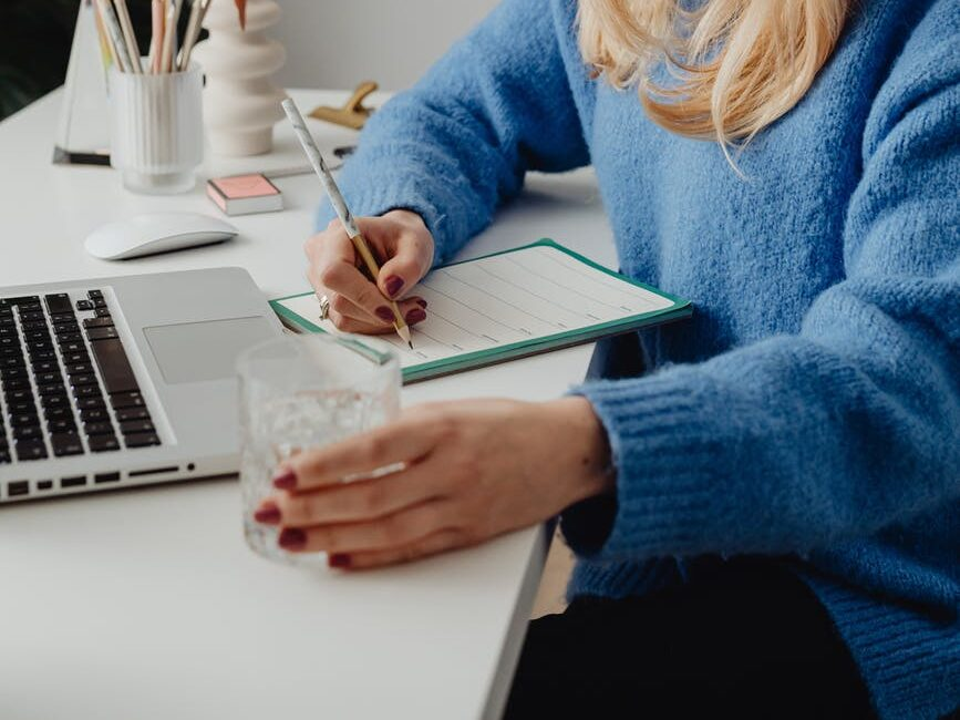 woman in blue sweater writing on her planner