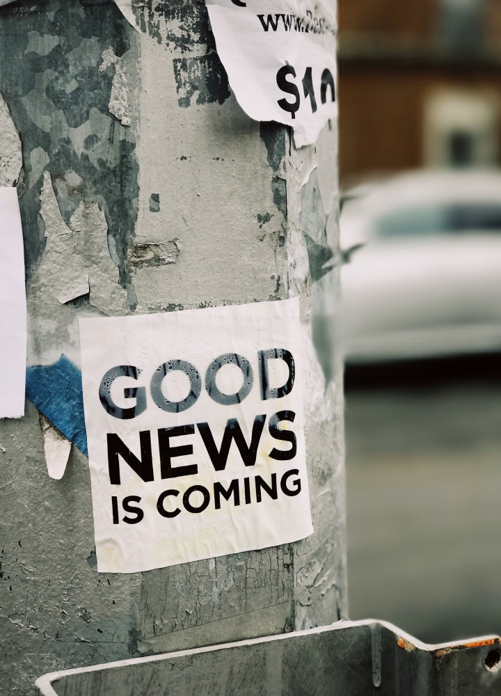 Picture saying 'Good News Is Coming' stuck to a lamp post