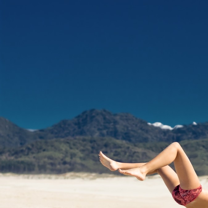 Woman's legs in the air on a beach