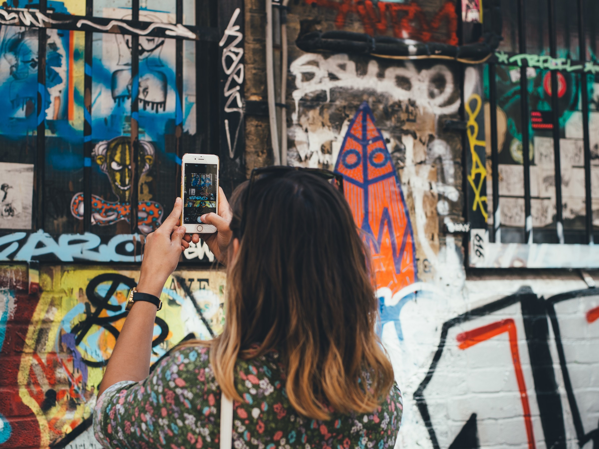 Woman taking pictures of graffiti using iphone