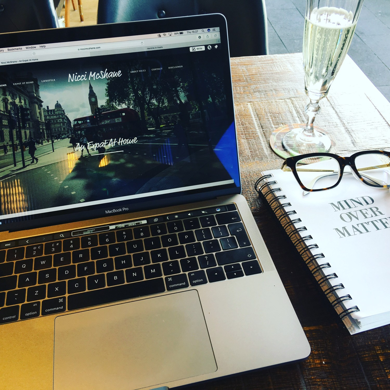 Laptop, blogging journal and glass of prosecco in a pub