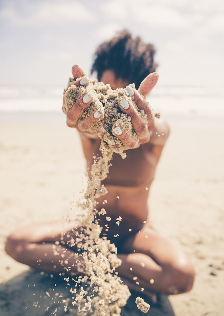 Woman in a bikini on a beach with arms stretched holding sand