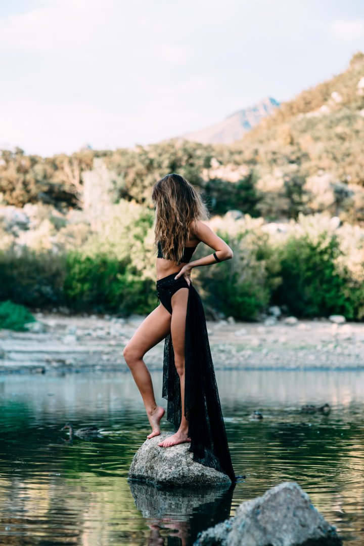 Woman stood on a stone in the middle of a lake doing a power pose