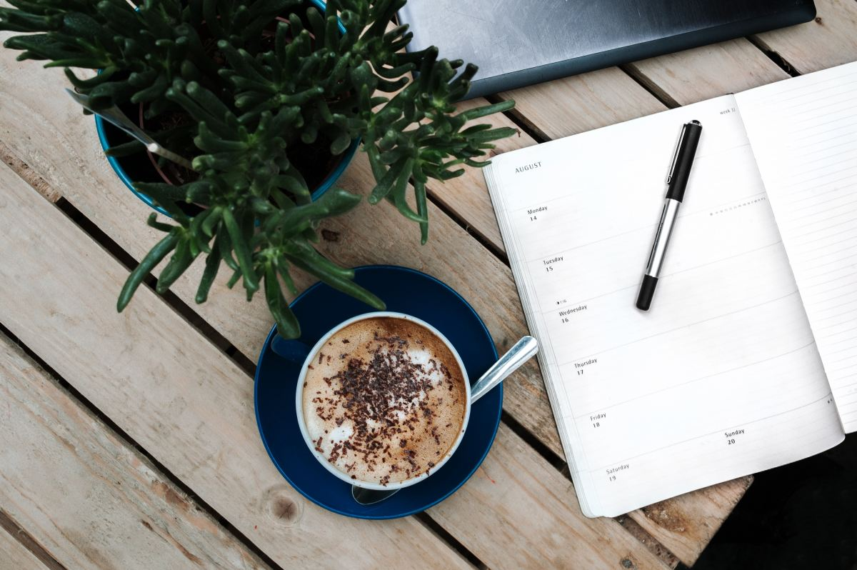 Picture of diary, coffee and plant on a wooden table