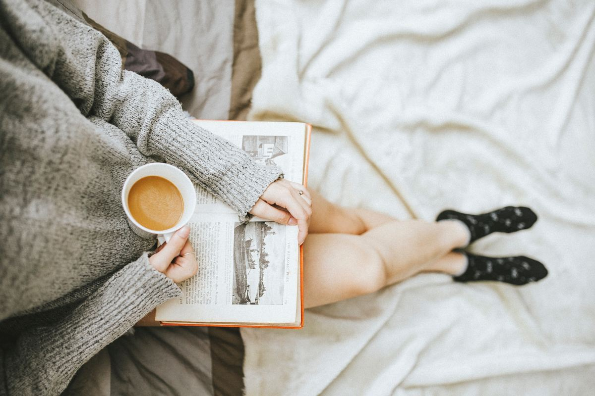 Photo of a girl reading a book on a bed with coffee