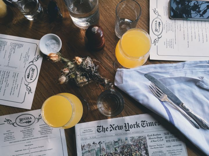 Picture of brunch table with orange and New York Times papers