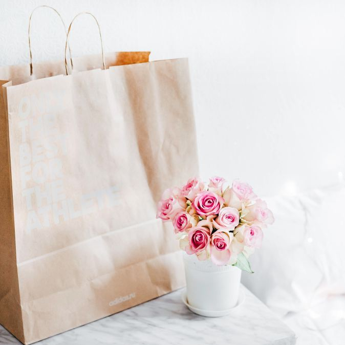 Picture of brown paper bag and a vase of pink roses