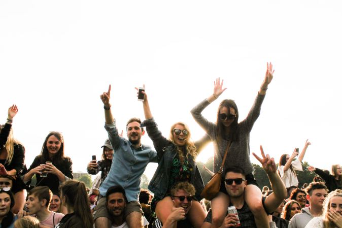 Picture of a group of happy friends with hands in the air