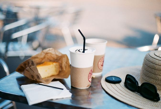 Picture of coffee and cake on table with sunglasses and a hat