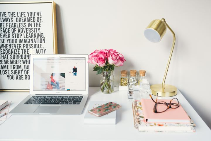 Picture of desk with laptop, lamp, pink and gold accessories