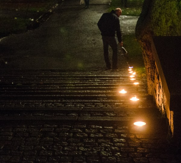 "Man lighting tea lights, ""bringing light to darkness"", downtown Stockholm. Photo credits: Jonathan Luedee"