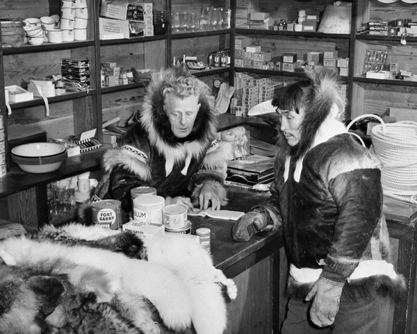 Leo Manning, manager at the Hudson's Bay Company trading post, lists the items exchanged for. Coppermine, N.W.T., [Kugluktuk (formerly Coppermine), Nunavut], 1949. Source: LAC