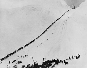 Miners and prospectors climb the Chilkoot Trail during the Klondike Gold Rush. Source: Wikimedia Commons. By Hegg, E.A (1867-1948). This image is available from Library and Archives Canada under the reproduction reference number C-005142 and under the MIKAN ID number 3192704.
