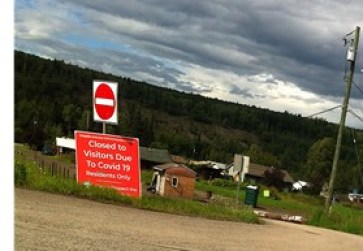 "Image of sign outside of Gitanmax, British Columbia that says ""Closed to Visitors Due to Covid 19"""