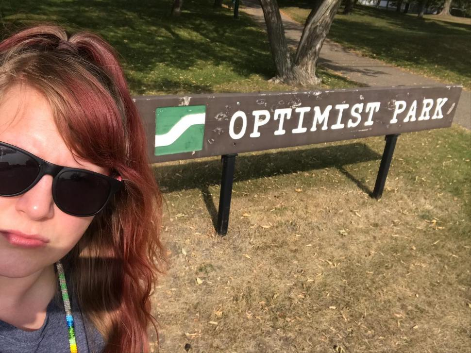 A woman with sunglasses and a frown on stands in front of the Optimist Park sign in Saskatoon, Saskatchewan.