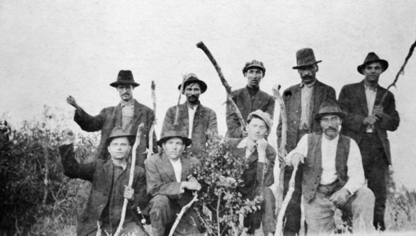 Nine coal miners posing with sticks.