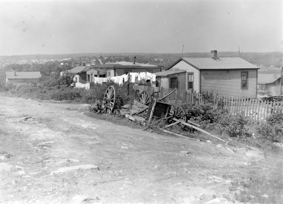 A dirt street lined with small wooden houses with laundry lines in front of them.