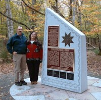 Two people stand beside the Commemorative monument at Kejimkujik National Park and National Historic site