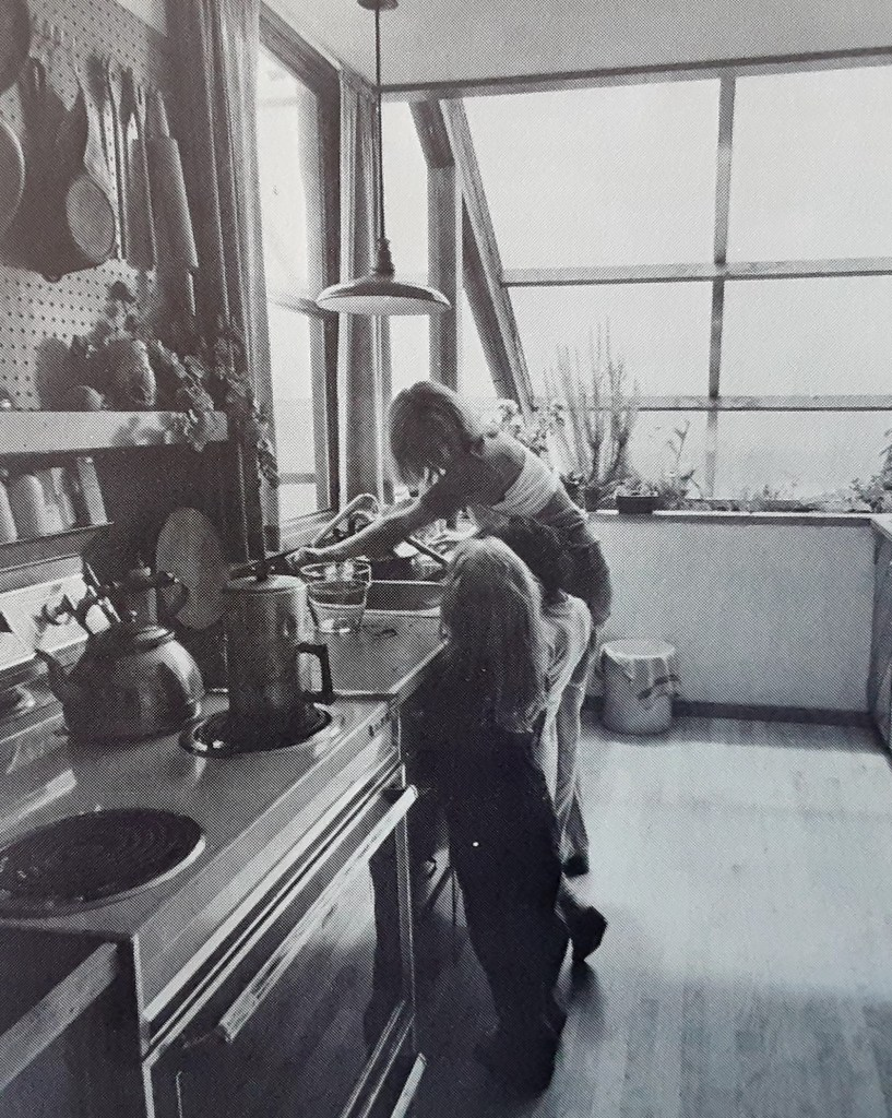 Black and white photograph in a kitchen. A young woman is talking to a young girl. They are standing at a sink. There is a stove in the foreground with a kettle and pot. In the background there are large windows, plants grow in front of them