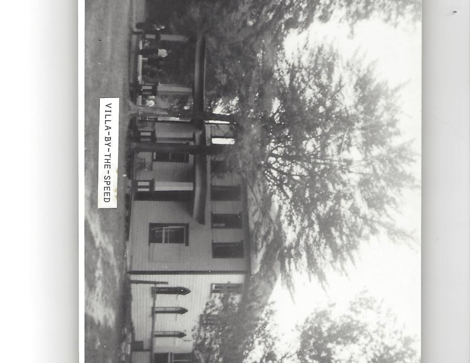 Black and white photograph of a house surrounded by trees, with people standing in the front porch.