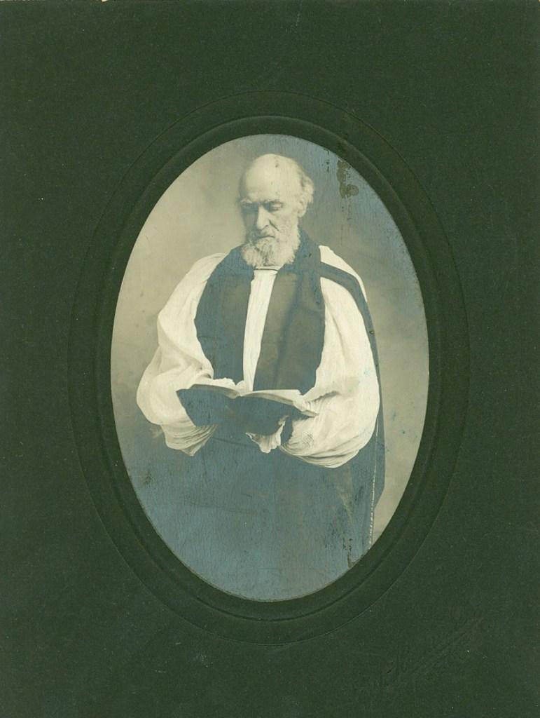 Older man in religious regalia reading a Bible