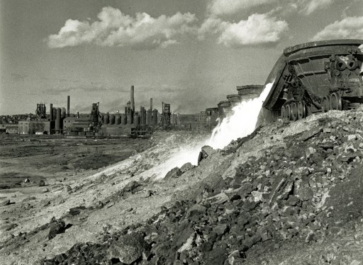 Dumping molten slag, with mill furnaces in background