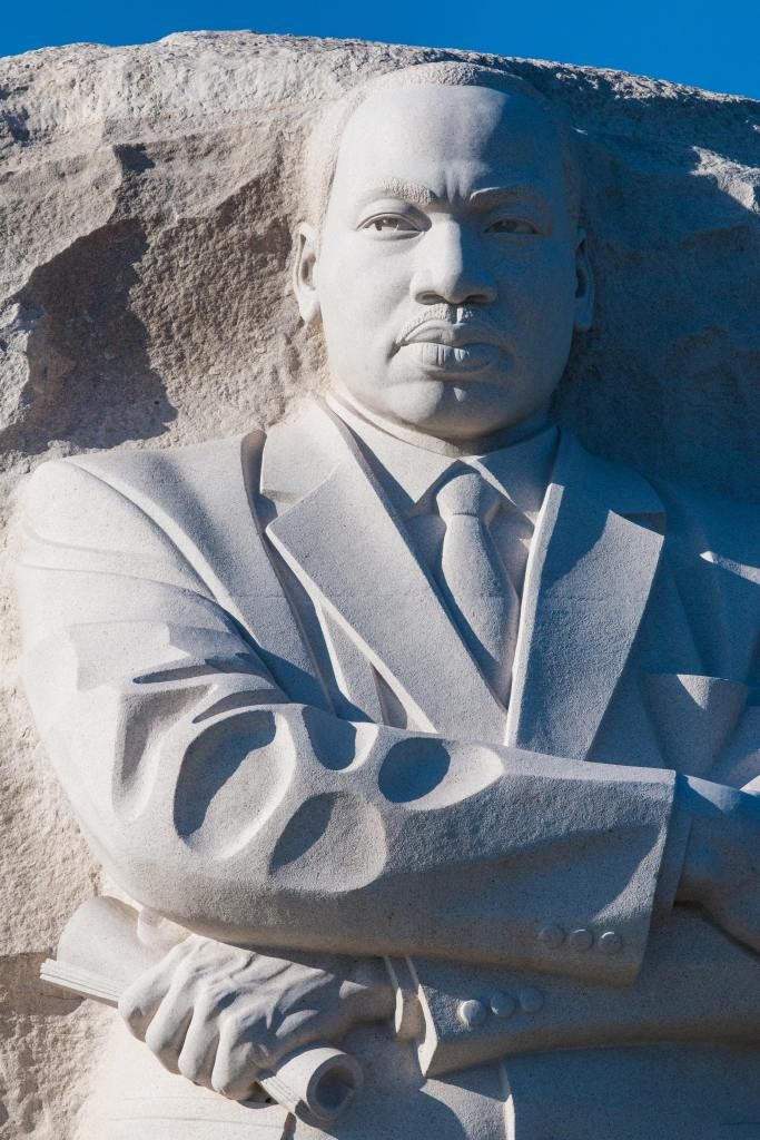 Monument sculpture of Dr. Martin Luther King Jr. features his upper body, arms crossed over his chest with a rolled document in his left hand.