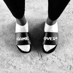 Overhead shot of white socks and black sandals with the word Game printed in white on broad black strap over top of one foot and the word Over duplicated on the other footon