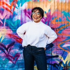 Woman laughing, wearing glasses mid-thirties in dark blue pants and white fleece top, hands behing her hips, black hair pulled back stands in front of turquoise brick wall painted with graphic swanlike brush strokes of purple, black ,orange, white, rose, yellow, and green hearts