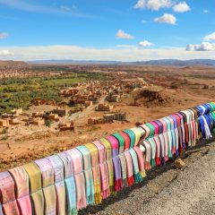 Colorful scarves on a guardrail overlooking a brown adobe landscape
