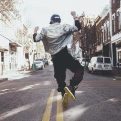 Backshot of man in black pants, black sneakers, white jacket and cap dancing in the center of the street next to two yellow parallel lineslines
