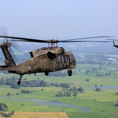 Two military helicopters in flight over landmass with one helicopter closeup shot