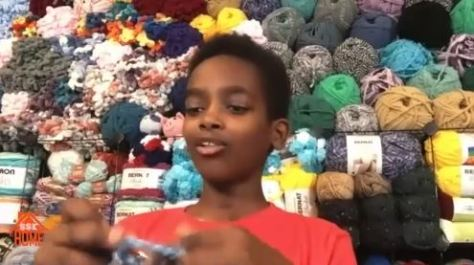 Ethiopian American boy sits and crotchets while background of colorful yarns are piled high in the background