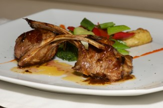 Lamb cutlets with vegetables on white plate