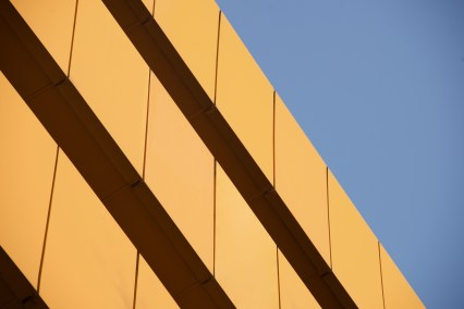 Wall of orange building against blue sky