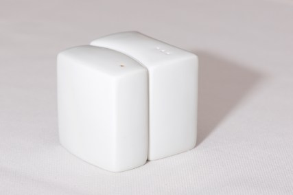Close-up of white salt and pepper shakers