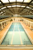 Drained indoor swimming pool with sun loungers