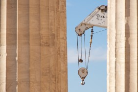 White crane between two marble Parthenon columns