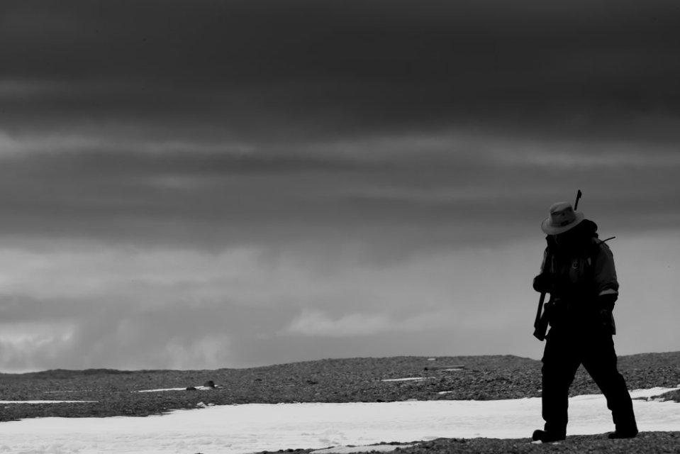 Black and white man walking with gun
