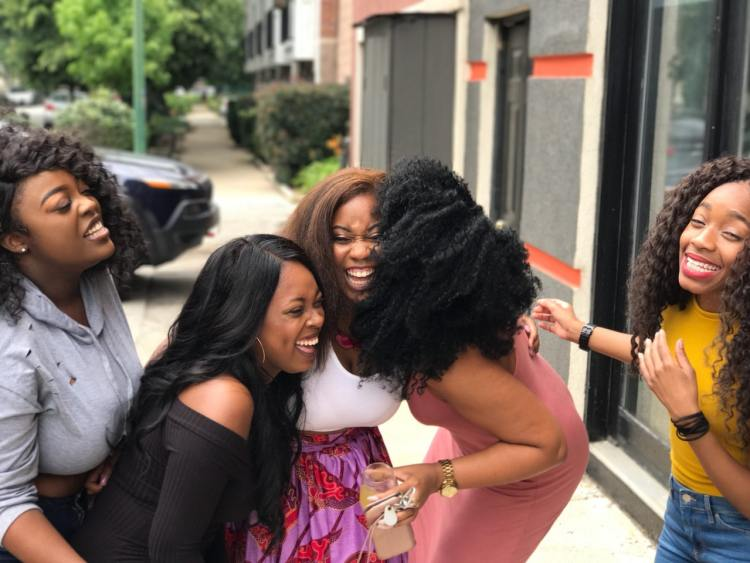 Image of friends laughing. Meeting social needs increases happiness.