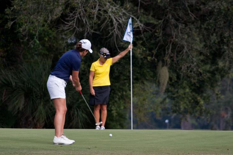 Image of two ladies playing golf. Having more leisure time increases happiness.