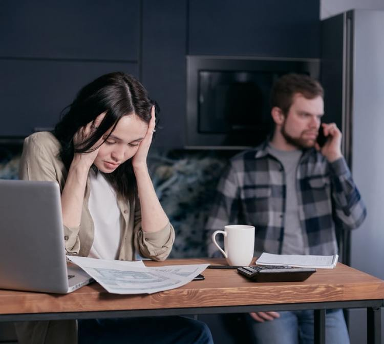 Image of two people worried about debt. Poor debt management is a habit that keeps you broke.