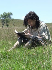Man reading his Bible in a field
