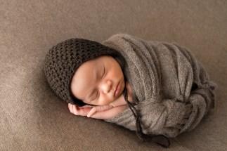 newborn baby boy wrapped in brown in a studio portrait by MN newborn photographer Nicki Joachim Photography Owatonna Minnesota