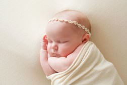 newborn baby girl wrapped in ivory with dainty head band in studio portrait taken by MN newborn photographer Nicki Joachim Photography Owatonna Minnesota