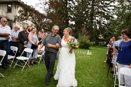 bride walking down the aisle with her father in country chic wedding portrait by MN wedding photographer Nicki Joachim Photography of Owatonna Minnesota