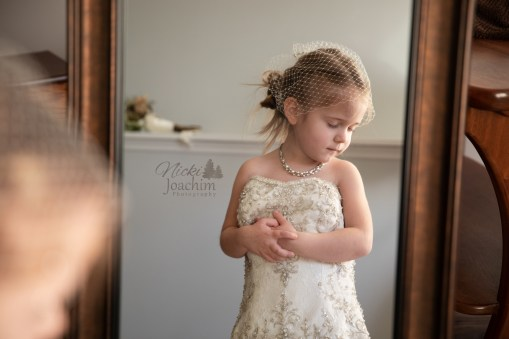 relaxed girl wearing her mother's wedding dress in lifestyle portrait by MN Wedding Photographer Nicki Joachim Photography of Owatonna, Minnesota
