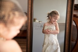 smiling girl wearing mother's wedding dress in a beautiul lifestyle portrait by MN Wedding Photographer Nicki Joachim Photography of Owatonna Minnesota